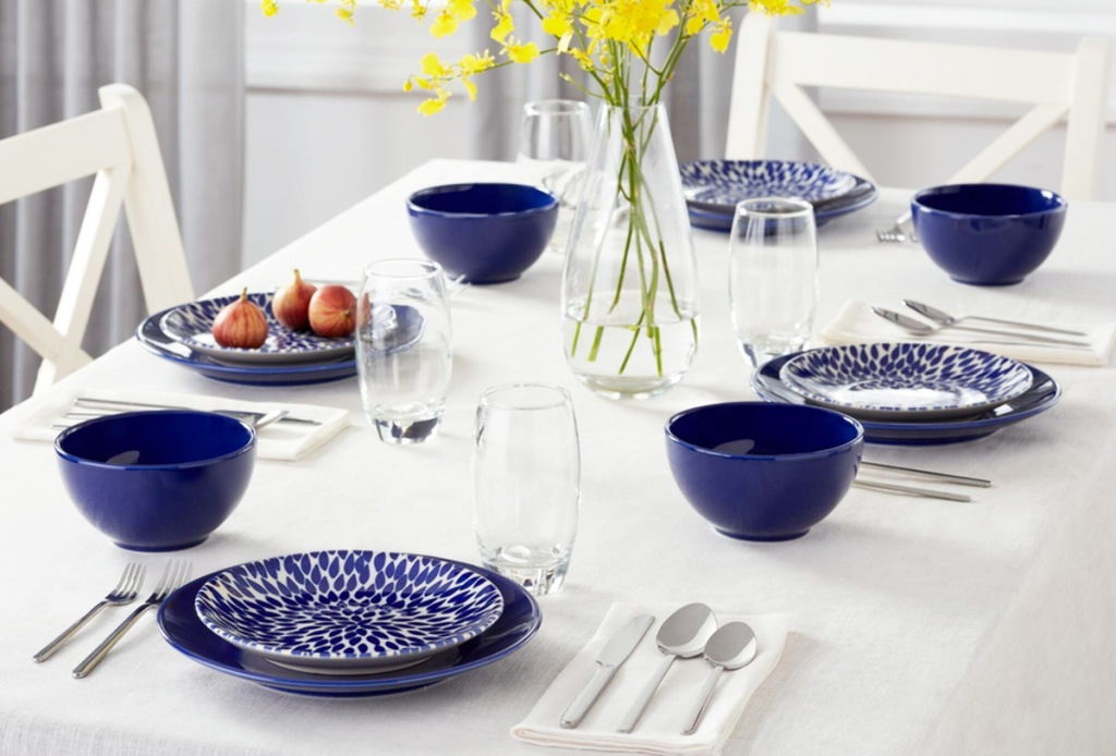 navy blue dinnerware set with four place settings on dinner table