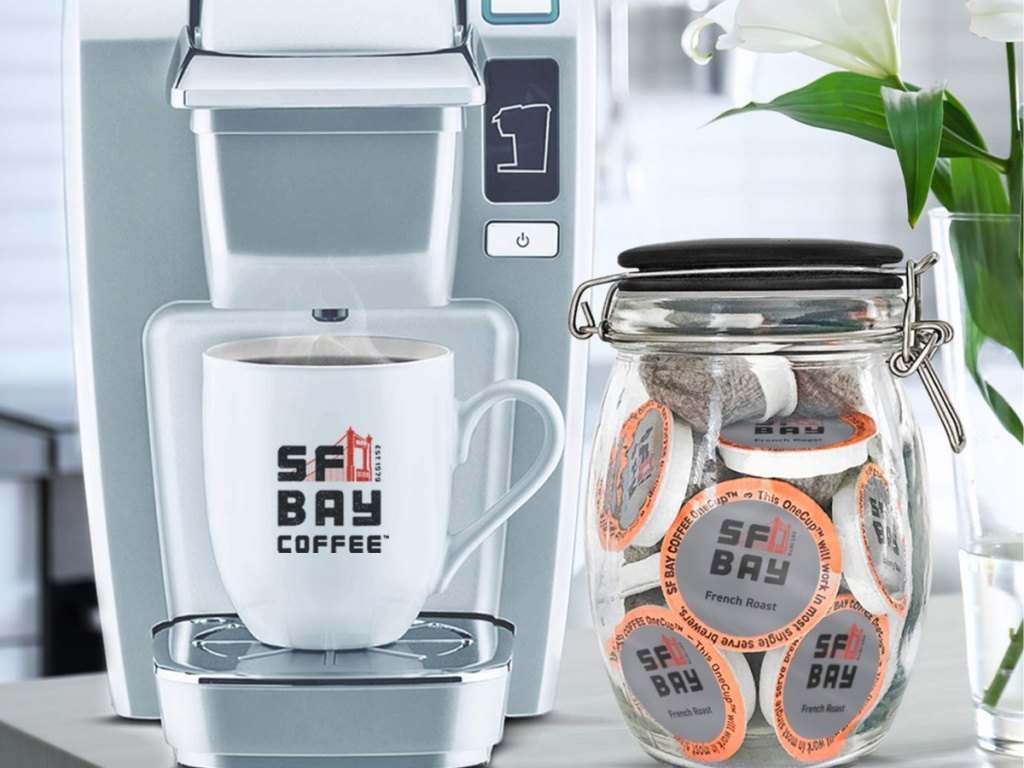 mug on silver coffee maker and container of french roast coffee pods on counter