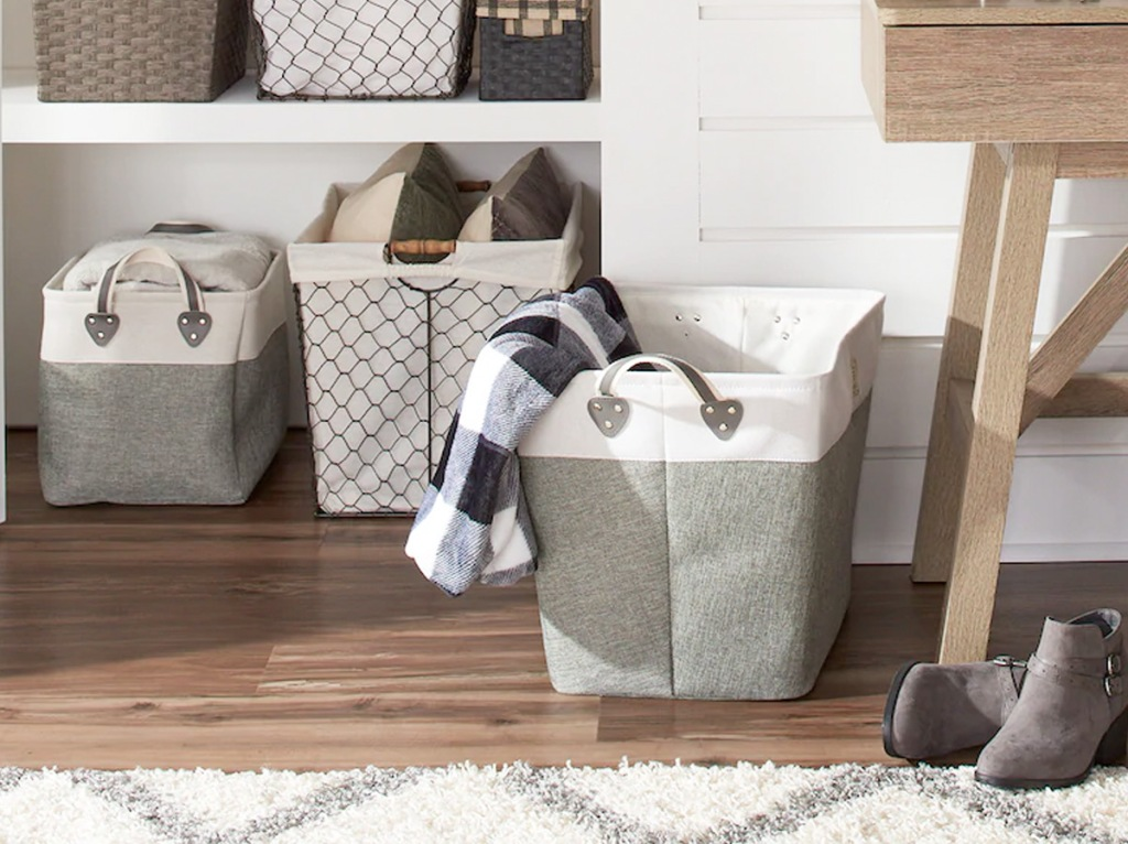 large grey and white fabric storage bin on floor next to built-in shleves full of other storage bins