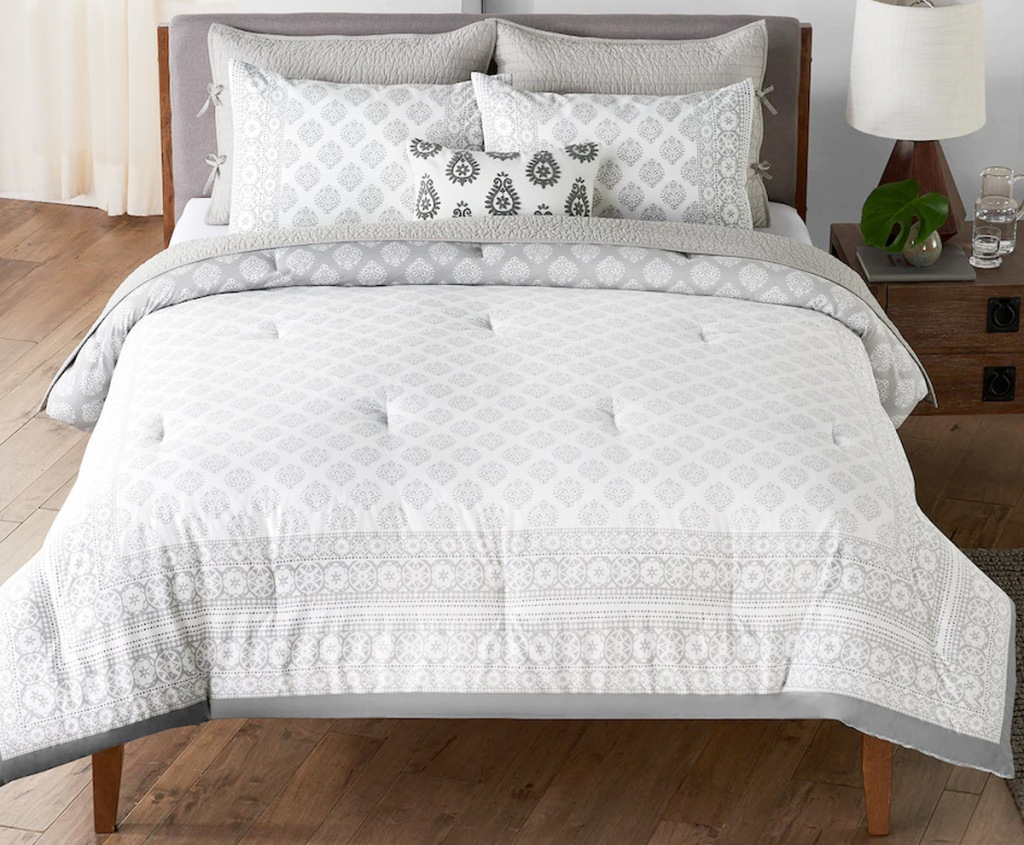 white and grey printed comforter set on a bed with pillows and matching throw pillow in center