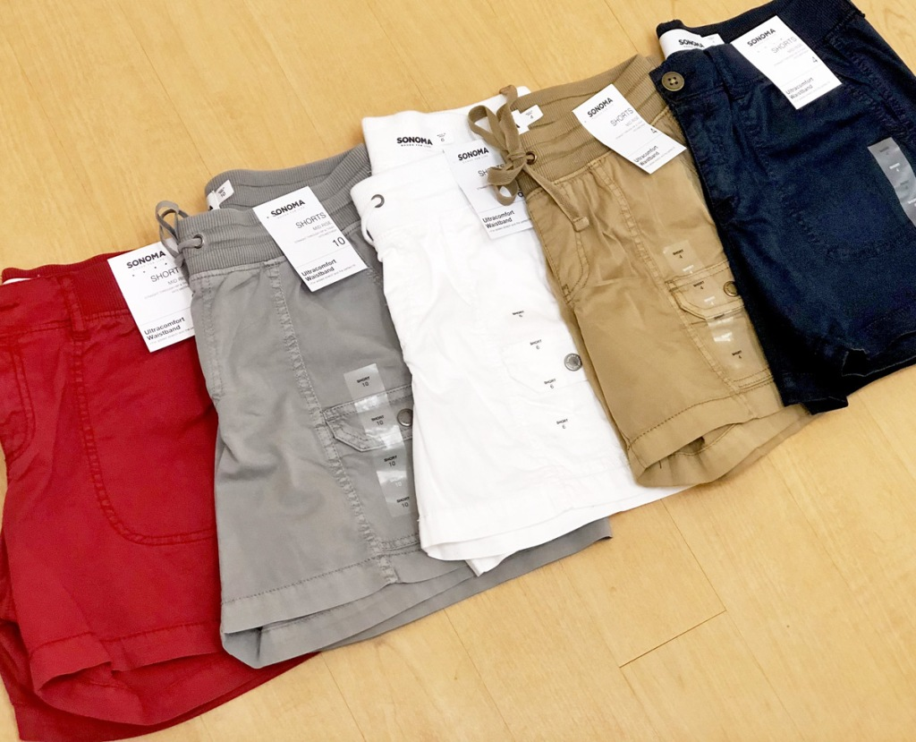multiple pairs of womens shorts in various colors laying on wood floor