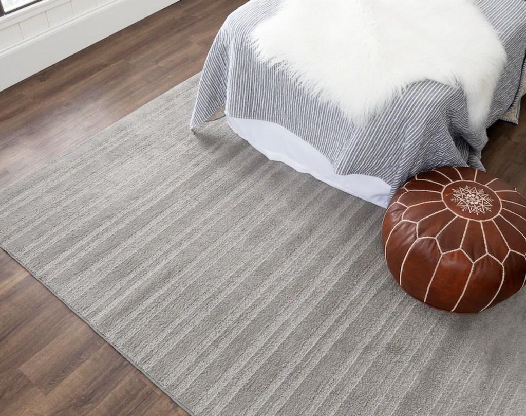 grey area rug under bed and ottoman on a hardwood floor