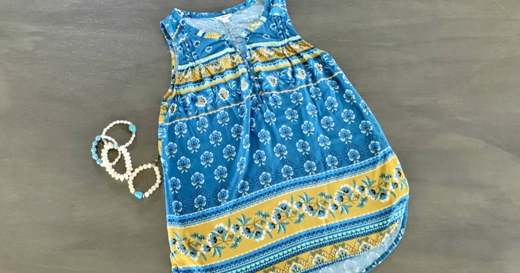 blue with yellow floral print womens tank top laying on grey floor with coordinating bracelets next to it