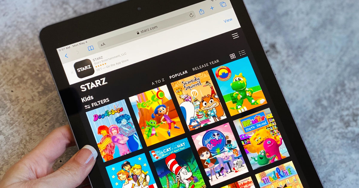 woman holding a black iPad showing the STARZ app and all the available kids shows