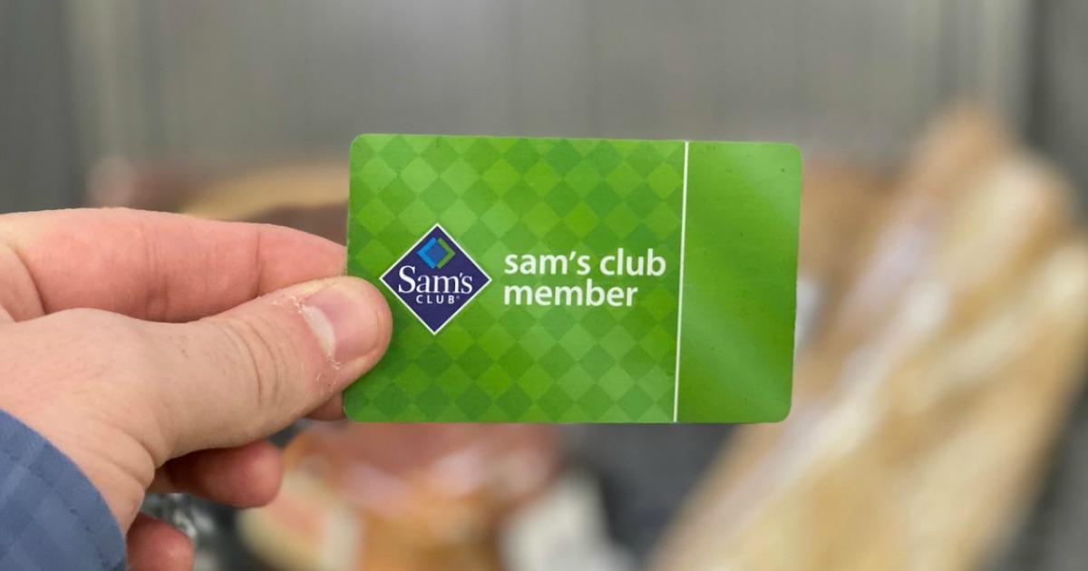 Man's hand holding a green Sam's Club Membership card near a shopping cart