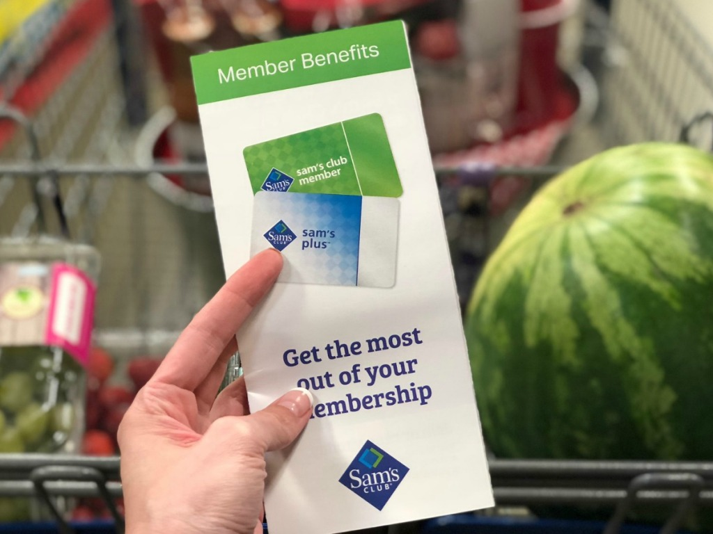 Hand holding a pamphlet for a Sam's Club Membership, in front of a shopping cart