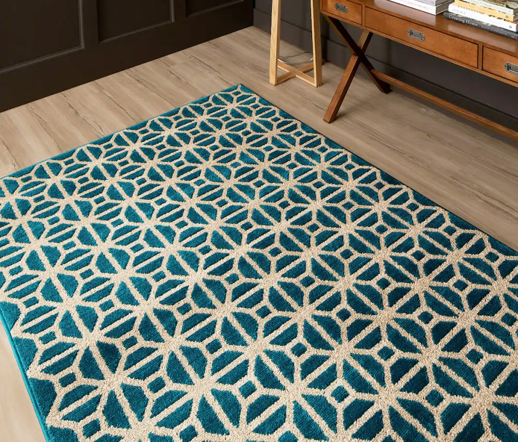 blue and cream colored abstract print area rug on hardwood floor