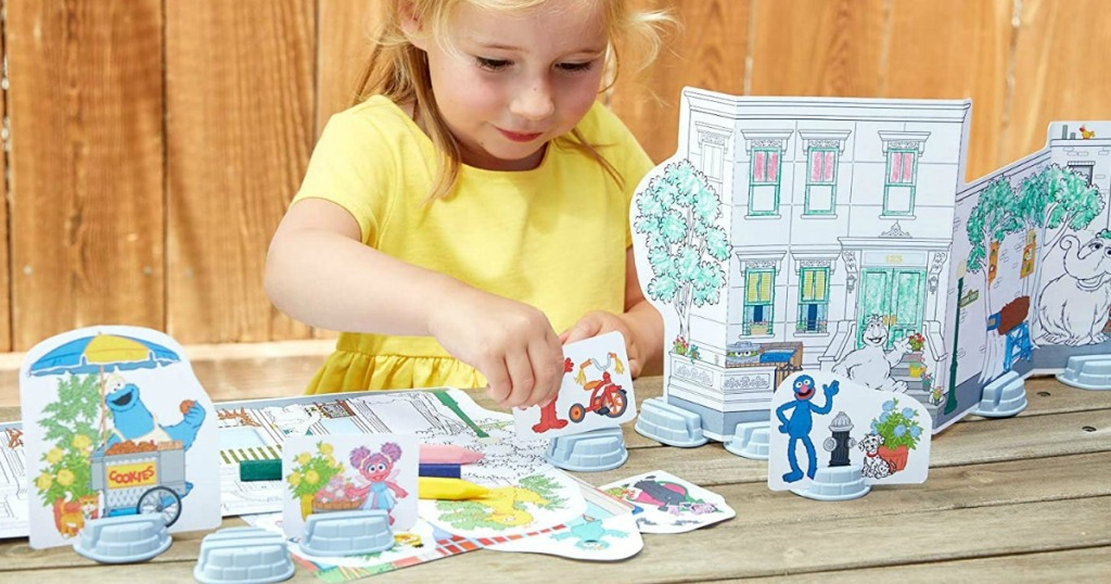 girl playing with a Sesame Street coloring set