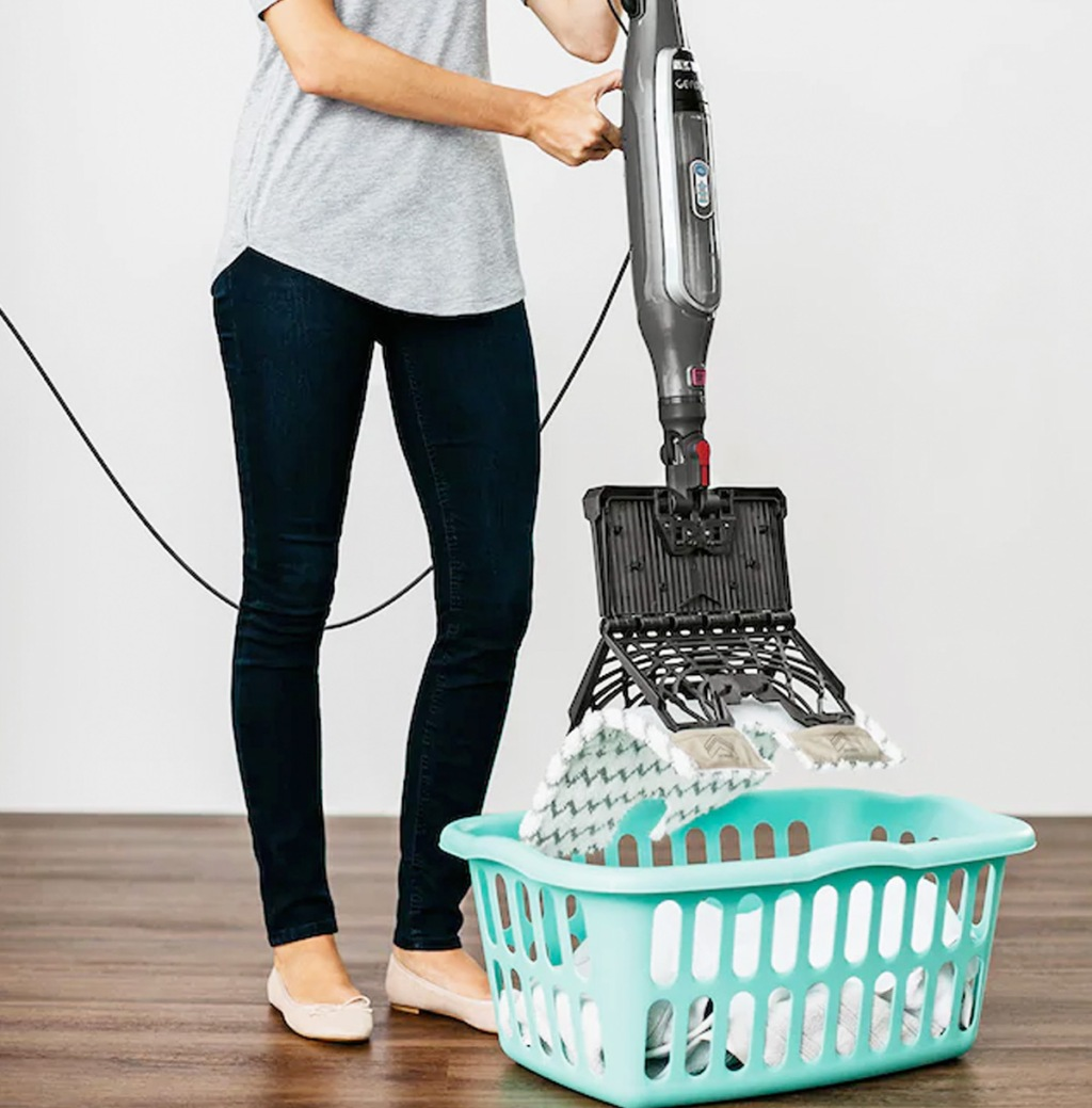 woman holding steam mop over blue laundry basket and pressing button to remove mop pad into basket