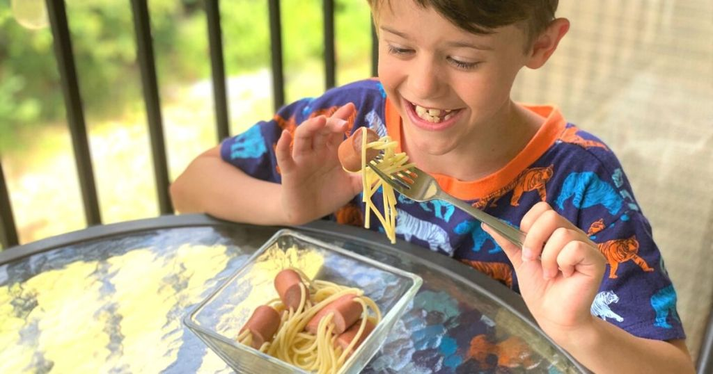 A little boy eating hot dog spaghetti at a table
