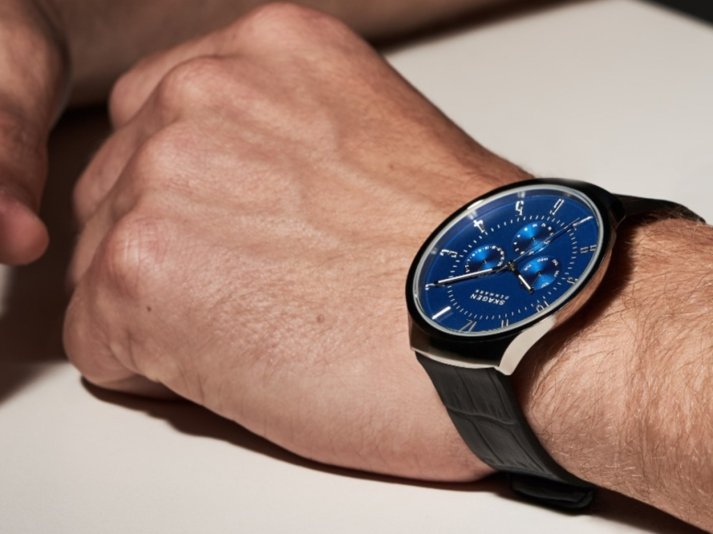 man wearing a watch with a blue face and black band