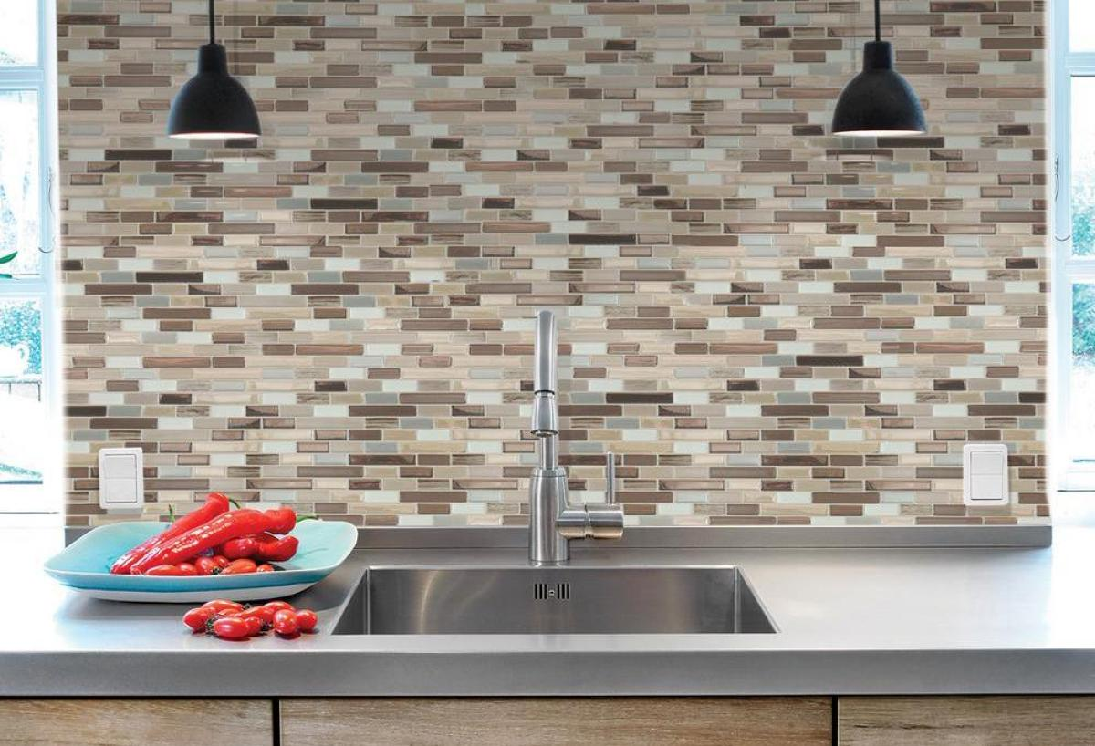kitchen sink with tiled wall behind it