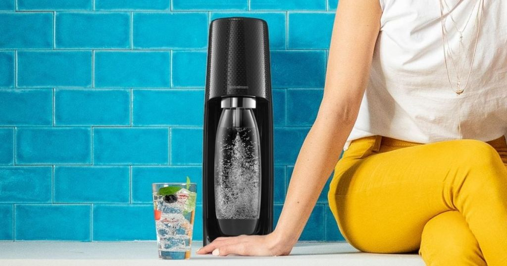 Sodastream machine on counter next to carbonated drink in glass and woman sitting on counter