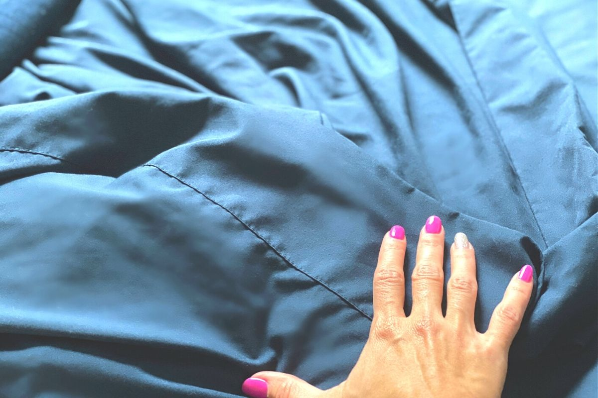 A hand feeling soft sheets on a bed