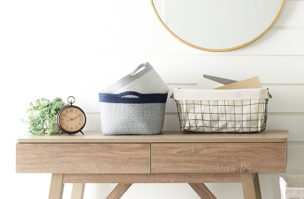 wire storage bin with white fabric liner and coiled rope baskets sitting on wood console table