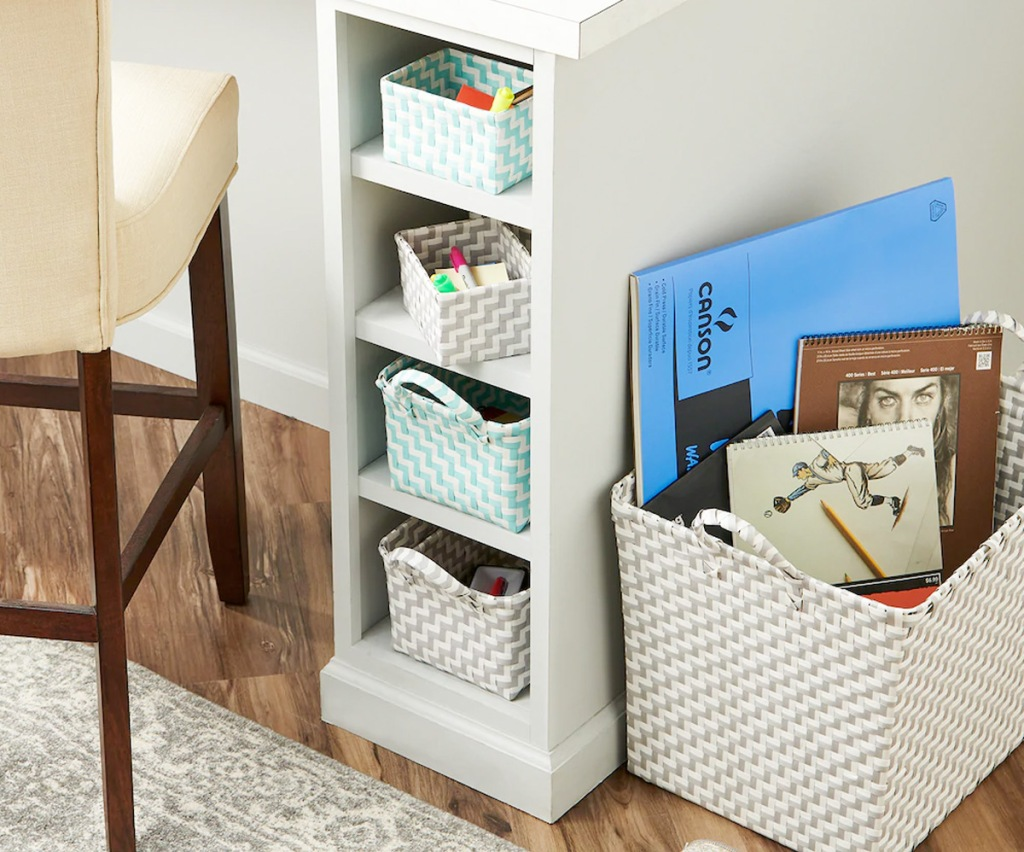 large woven rectangular storage bin on floor next to white desk with mini matching storage bins in cubbies