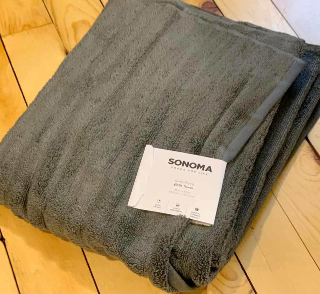 grey ribbed bath towel folded on wood floor with white tag on it