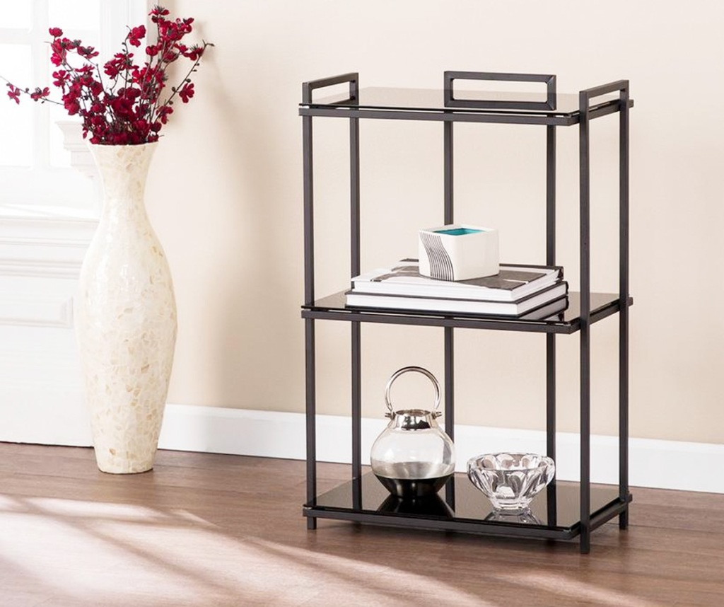 three tier glass bookcase with black metal frame on hardwood floor near large vase of red flowers