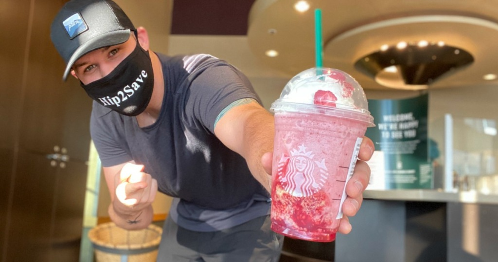 Man with Hip2Save mask holding pink colored Starbucks Frappucino drink