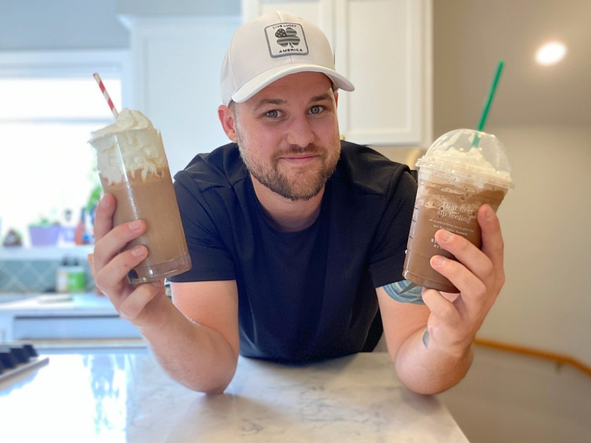 man holding Starbucks frappuccino and dupe in each hand
