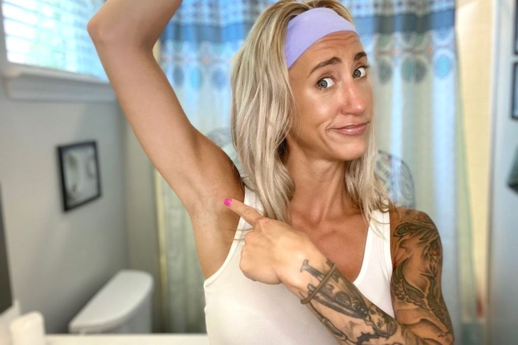 A woman pointing to her armpit