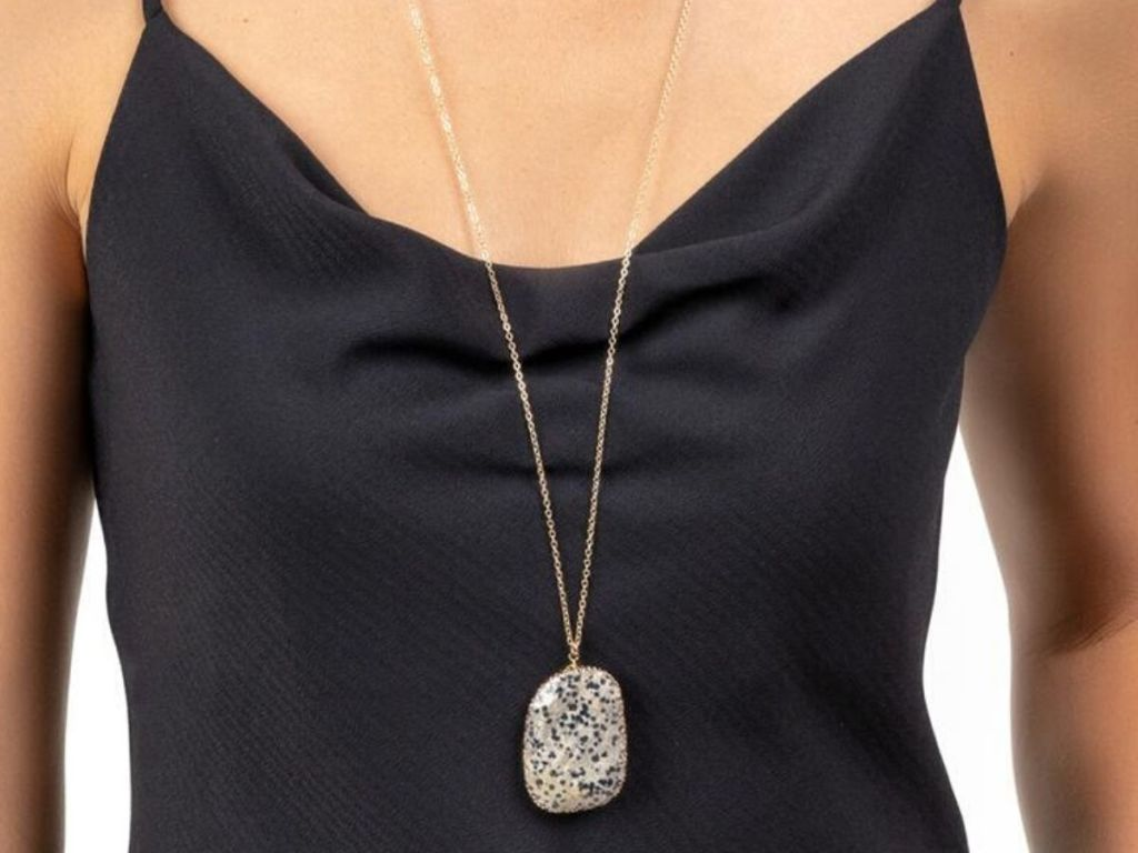 woman wearing long pendant style necklace