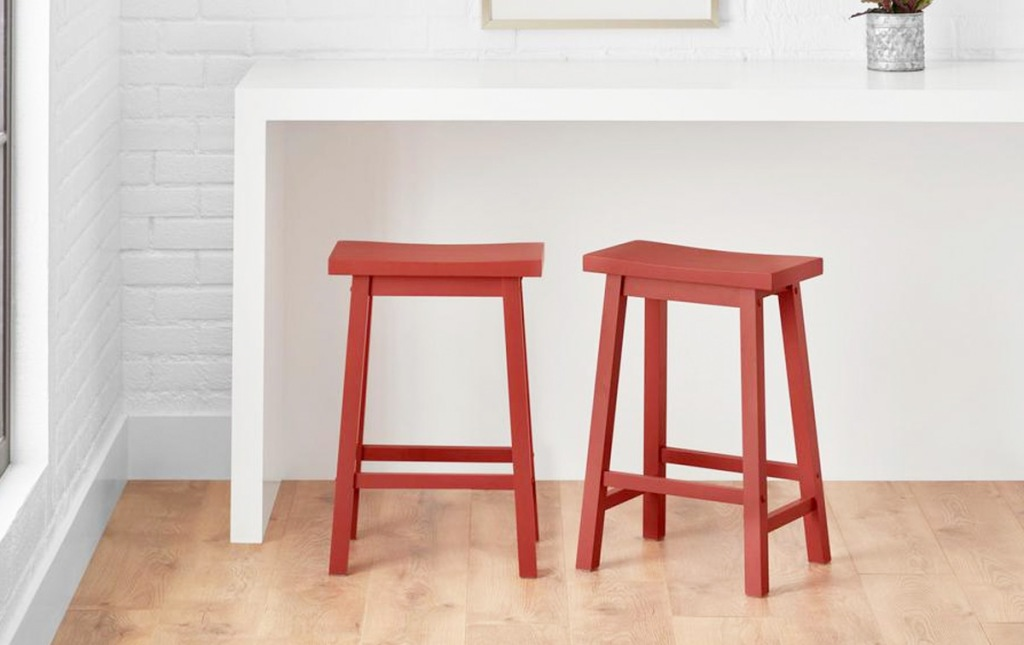 two red saddle style backless barstools