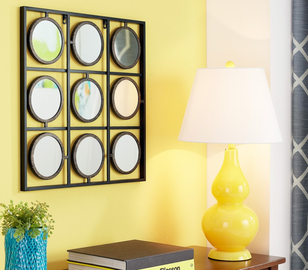 black square frame with nine circular mirrors inside hanging on a yellow wall near yellow lamp