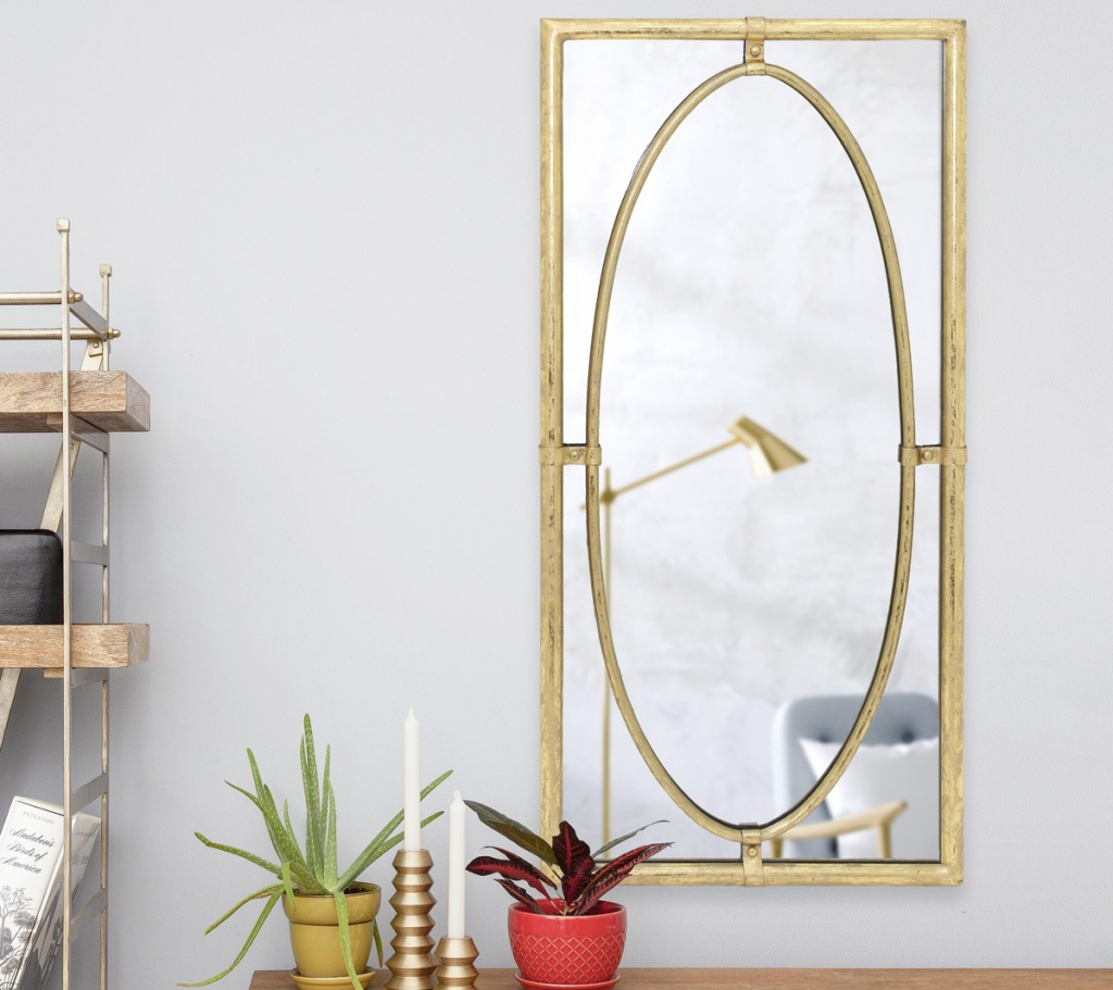 gold framed rectangular mirror with smaller oval inside on a white wall