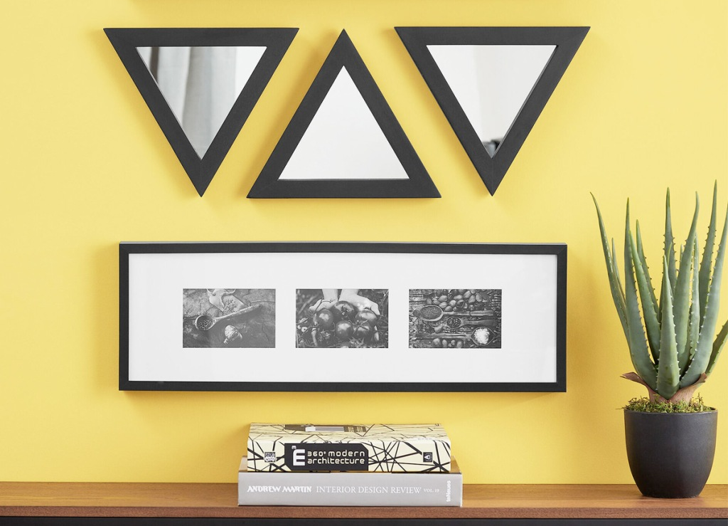 three triangle shaped mirrors on yellow wall above framed photo