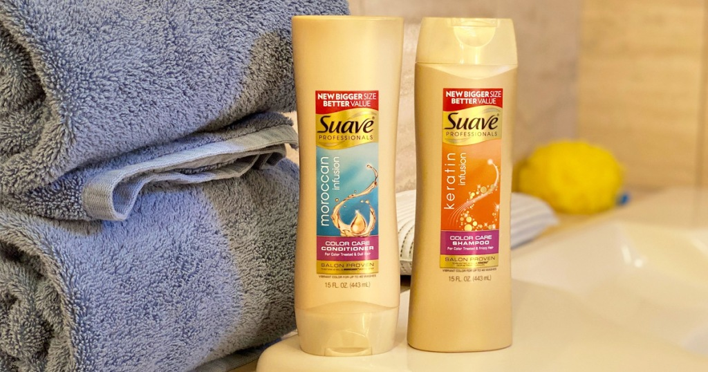 two gold bottles of suave professionals shampoo and conditioner sitting on edge of tub next to blue folded towels