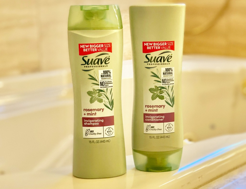 two green bottles of suave professionals shampoo and conditioner sitting on edge of tub