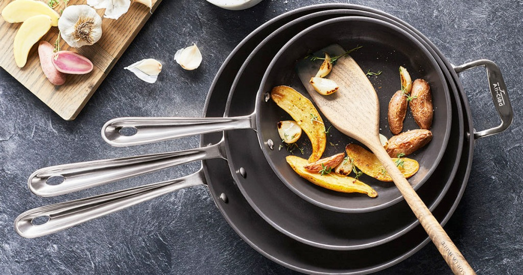 set of three black frying pans stacked into one another with roasted peppers and wooden spoon