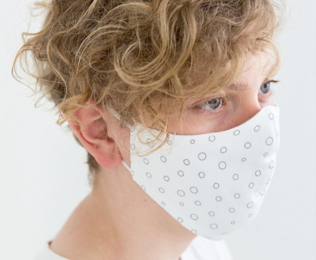 teen boy wearing white face mask with black bubble dot print