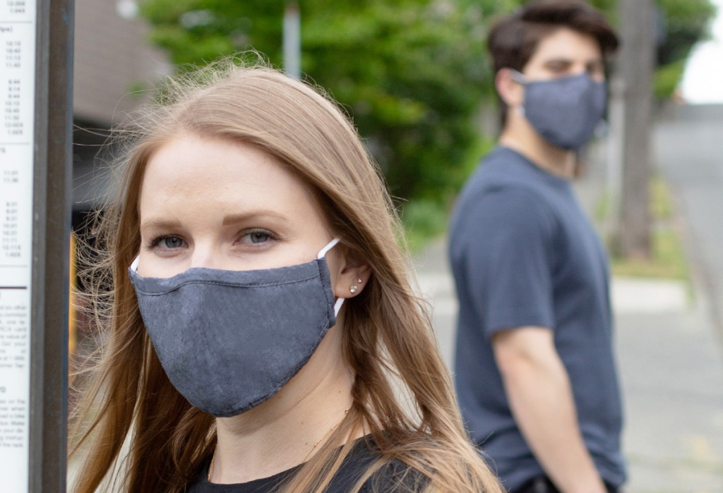 woman and man standing outside wearing matching grey face masks