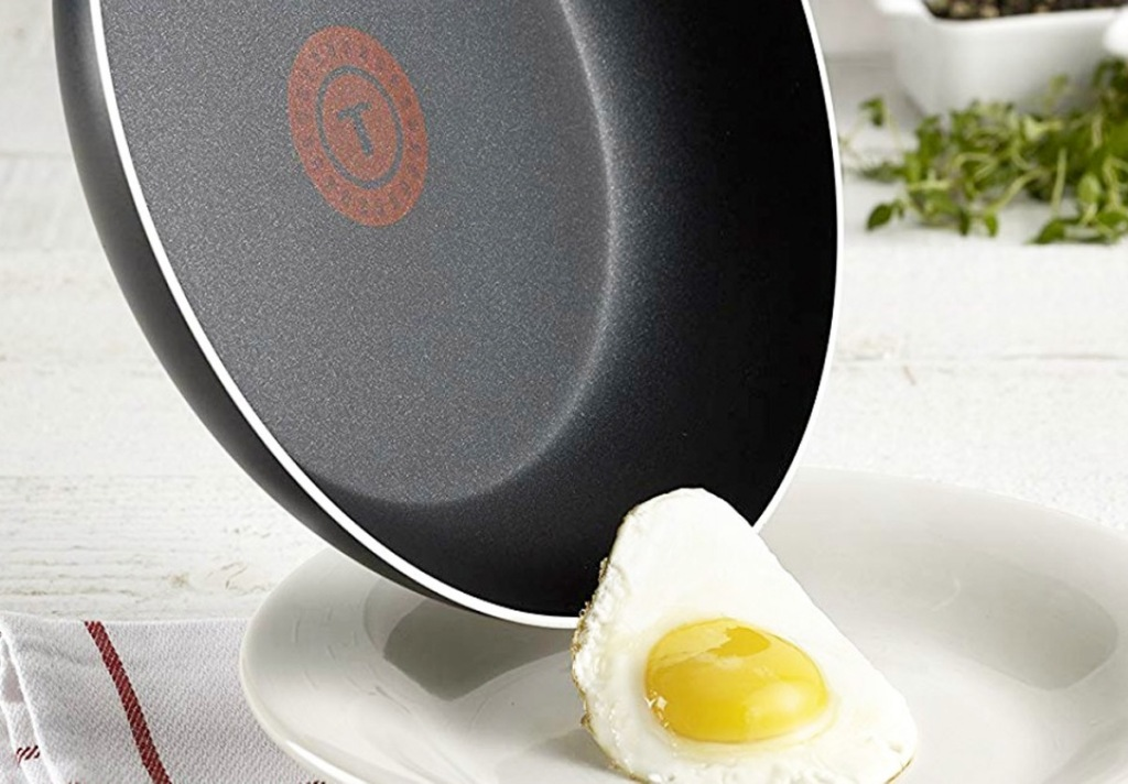 black frying pan with egg sliding out of it onto plate