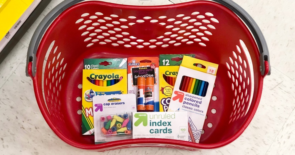 red plastic shopping basket with various school supplies inside