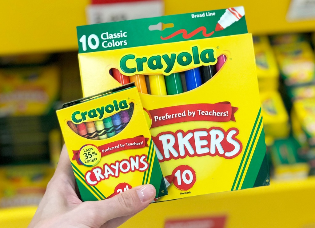 person holding yellow and green boxes of crayola crayons and markers