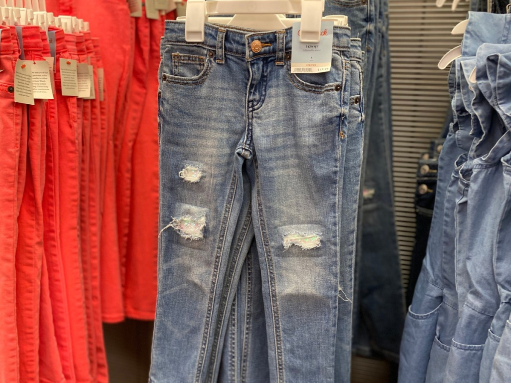 Girls skinny jeans on a hanger next to other jeans