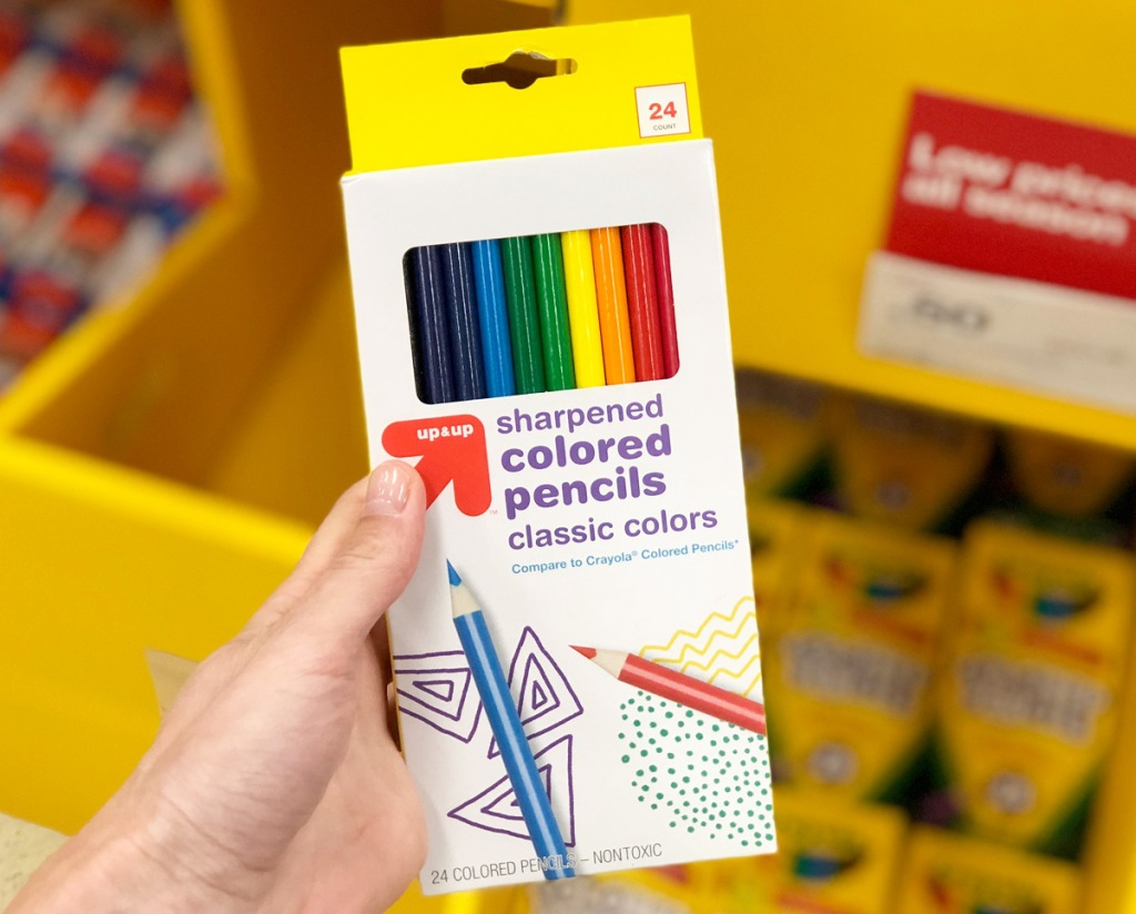 person holding a yellow and white 10-count package of colored pencils