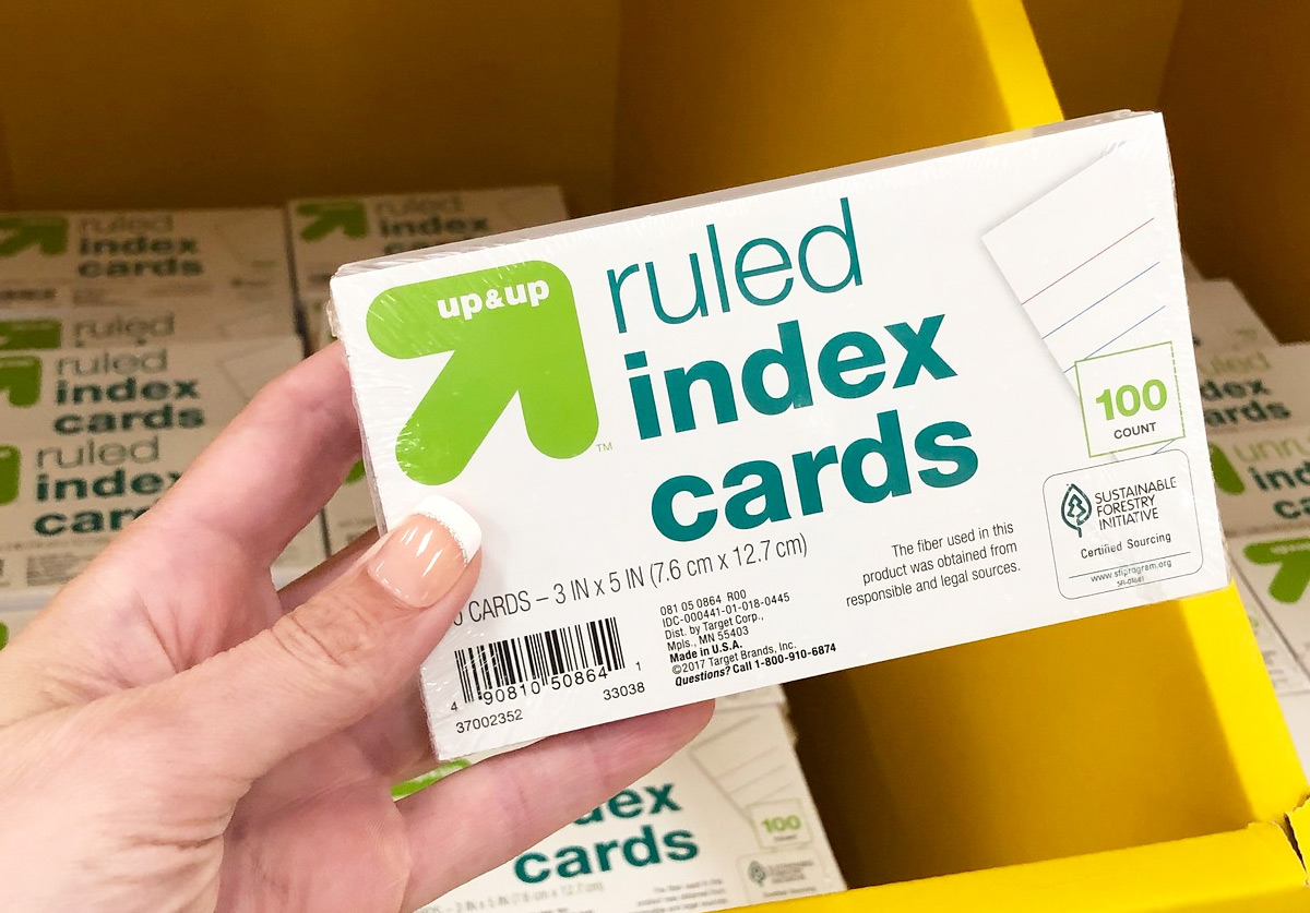 person holding a package of ruled index cards