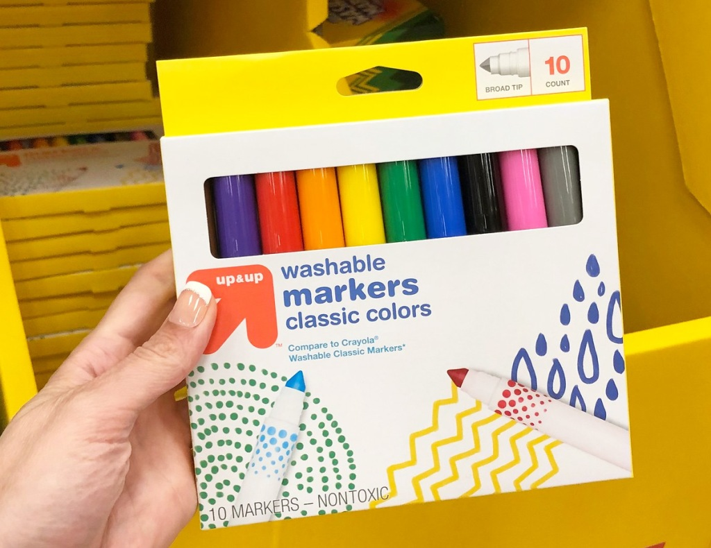 person holding a yellow and white package of assorted colored markers