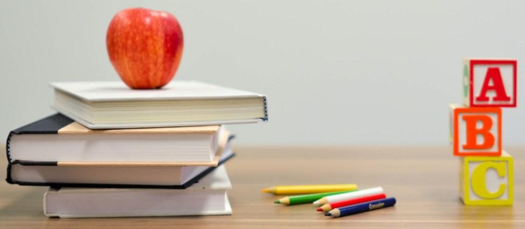 books, apple, pencils, and letter blocks on desk