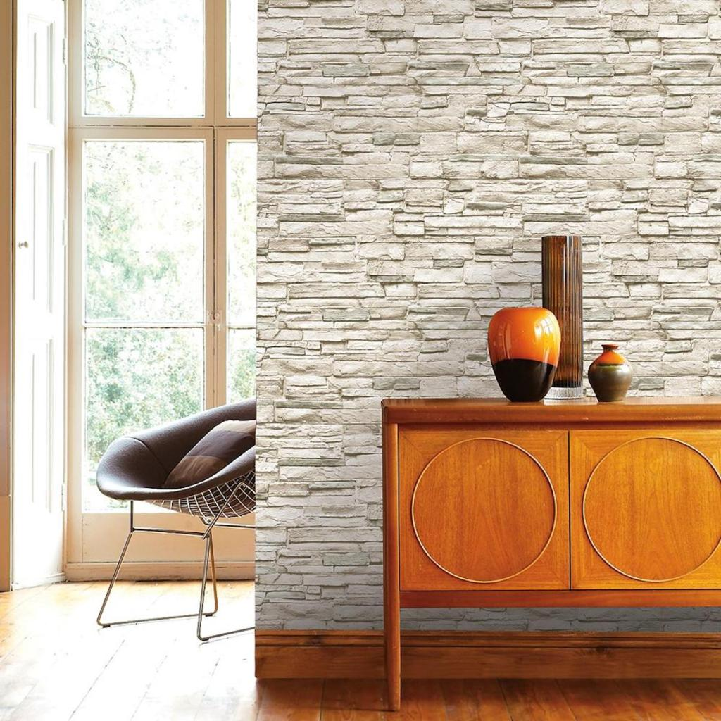 Tempaper Light Stone Ivory Peel and Stick Wallpaper on accent wall with wood wall table with decorative pieces on the table
