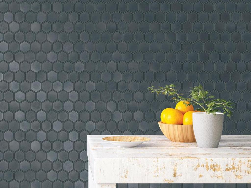 dark colored Tempaper Hexagon Tiles Gunmetal Peel and Stick Wallpaper on wall with wood farmhouse like table with bowl of lemons