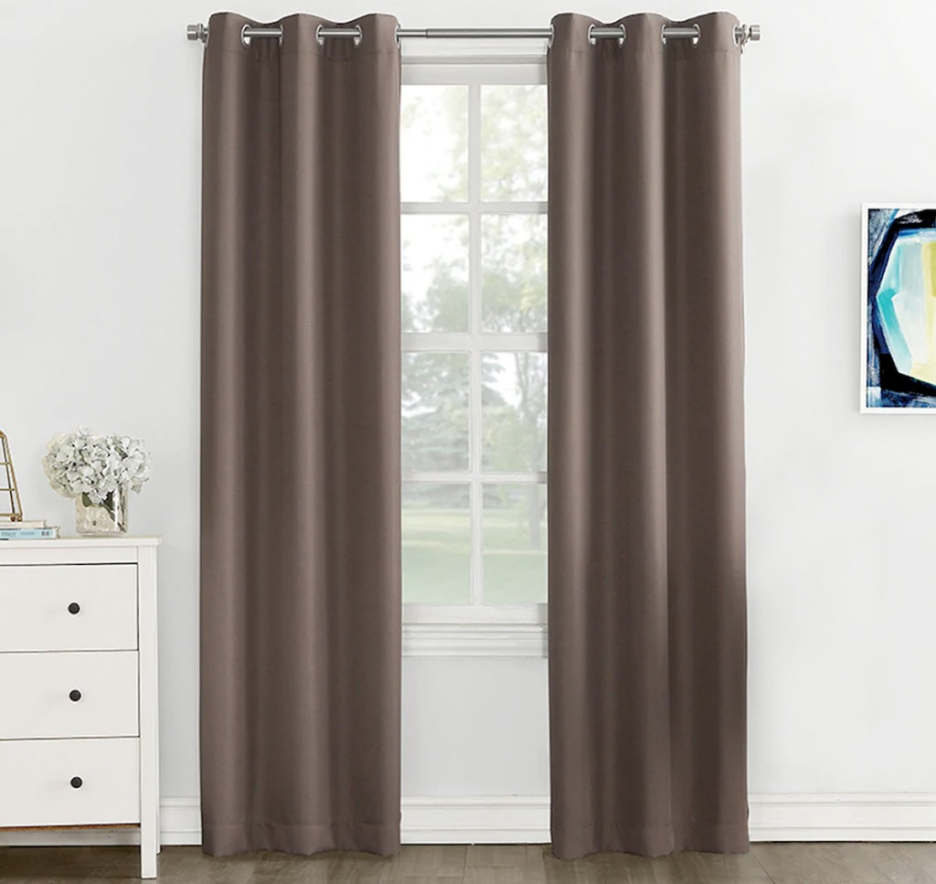 two solid brown curtain panels on curtain rod in front of window