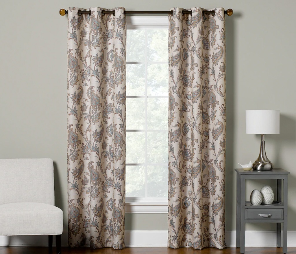 two brown and cream floral print curtain panels on curtain rod in front of window