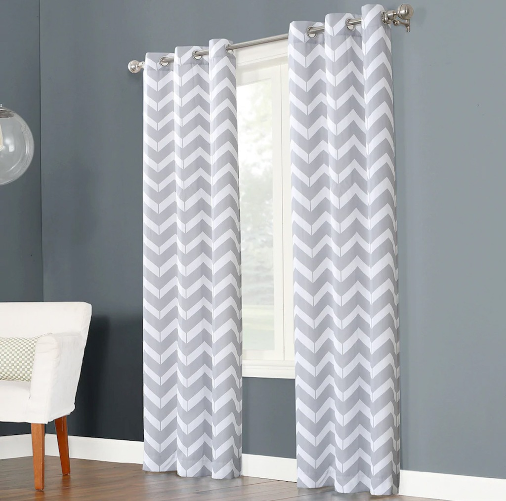 two grey and white chevron print curtain panels on curtain rod in front of window