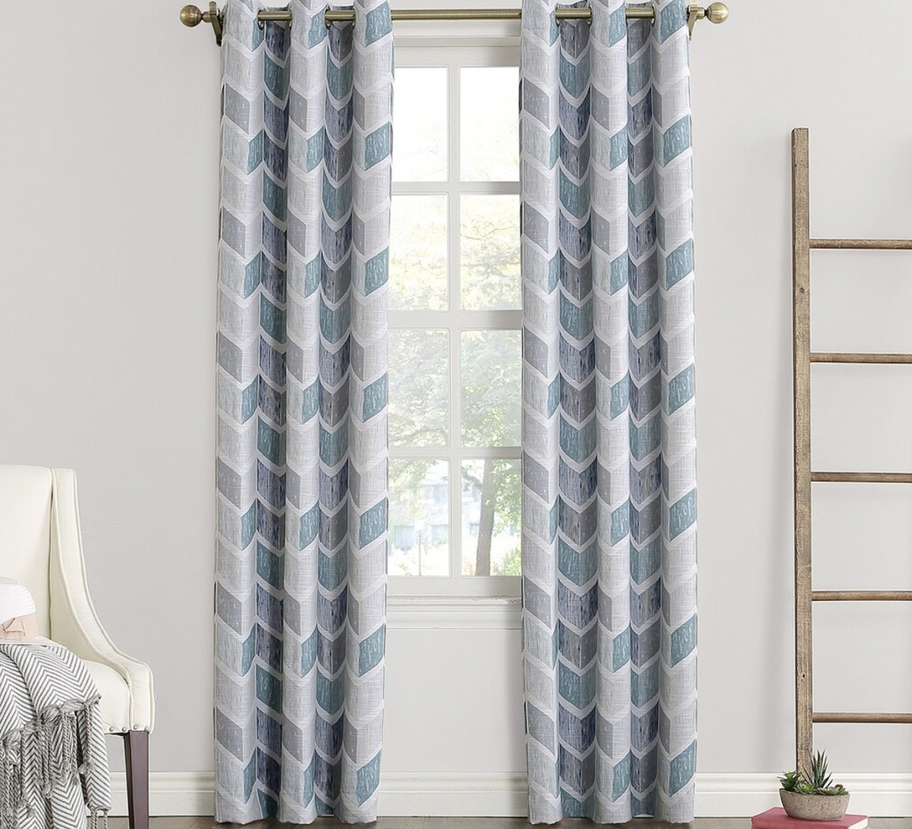 two blue, white, and grey chevron print curtain panels on curtain rod in front of window