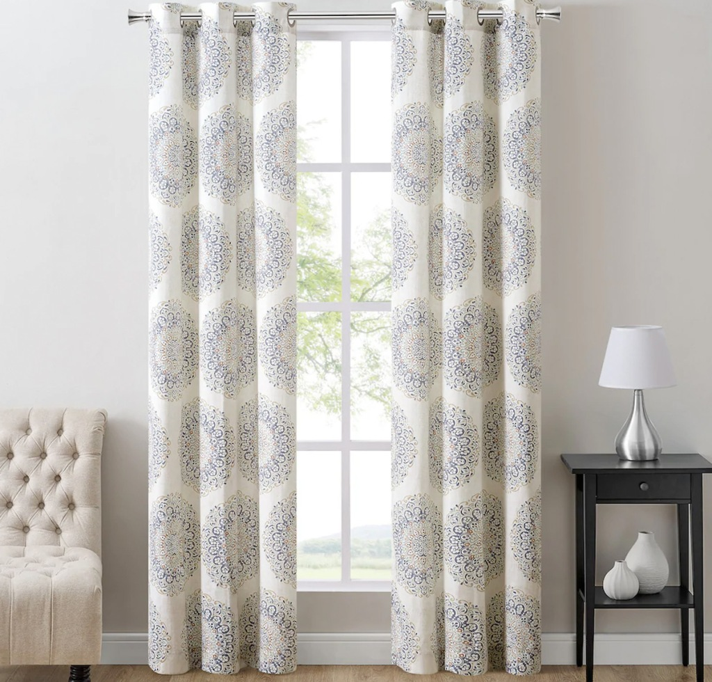two grey, blue, and white floral medallion print curtain panels on curtain rod in front of window